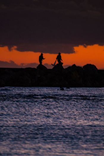 Silhouette people on sea against sky during sunset