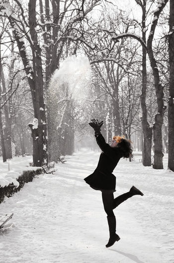 Full Length Of Woman Playing With Snow In Forest