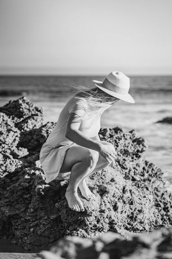 Woman on rock by sea against sky