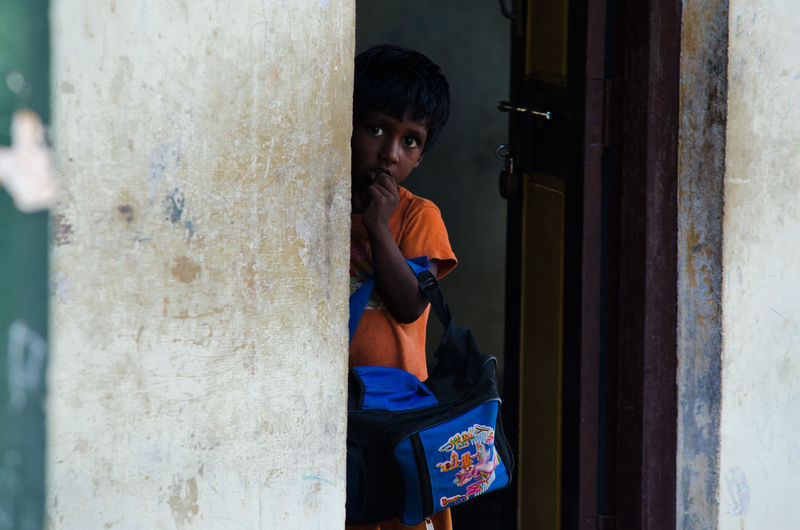 A school child hides from the camera in a small rural village in Tamil Nadu, India. Children India Indian Indian Culture  PortraitPhotography Portraits Casual Clothing Child Childhood Day Hide Hide And Seek Indiapictures One Person Outdoors People Portrait Portrait Photography Portraiture Real People School Shy Standing