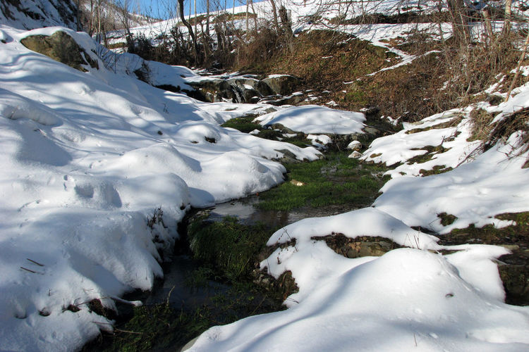 Beauty In Nature Cold Temperature Day Environment Flowing Flowing Water Landscape Mountain Nature No People Non-urban Scene Outdoors Plant Rock Scenics - Nature Snow Snowcapped Mountain Tranquil Scene Tranquility Water White Color Winter