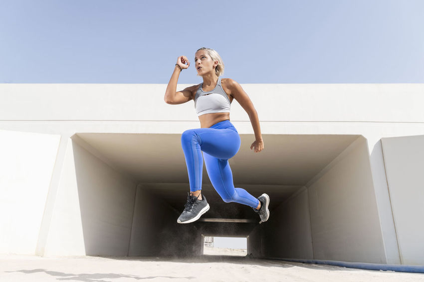 Middle Eastern Girl with short braided hair exercising in a urban setting with a tunnel in the back ground wearing blue and gray fitness outfit on a hot bright sunny day. Exercising Jumping Off Rocks Sitting Beautiful Woman Blue Bright Day Day Dusty Emotion Fitness Model Front View Full Length Happiness Hot Day ☀ Leisure Activity Lifestyles Middle Eastern Woman Nature One Person Outdoors Real People Sitting Sky Smiling Sports Clothing Stretching Sunlight Sunny Young Adult Young Women