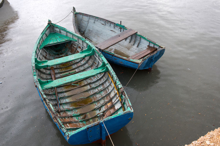 Vintage fishing boats on water in a rainy day Fishing Boats Malta Transportation Abandoned Boat Boats Day Fishing Fishing Boat Fishing Industry Floating On Water High Angle View Lake Mode Of Transportation Moored Nautical Vessel No People Rope Rowboat Rusty Sea Transportation Vessel Vessel In Port Water