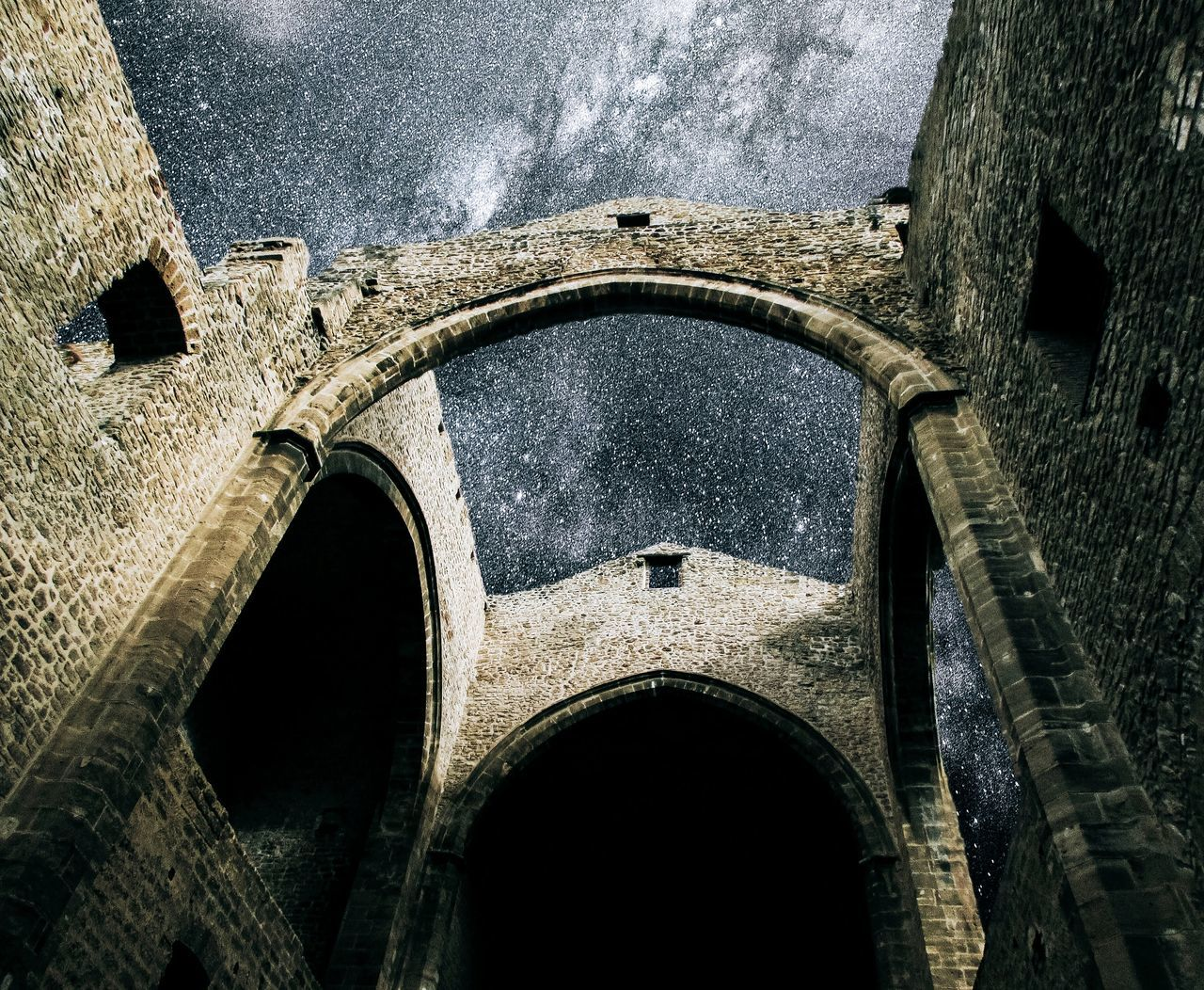 Low angle view of arched structure against the sky