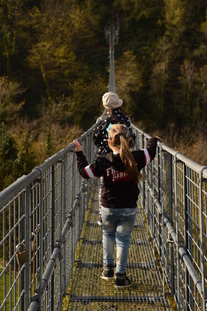The suspension bridge Adventure Autumn Colors Deepfield Forest Hiking Little Girls Long Narrow Suspension Bridge Trees Walking People And Places This Is Family