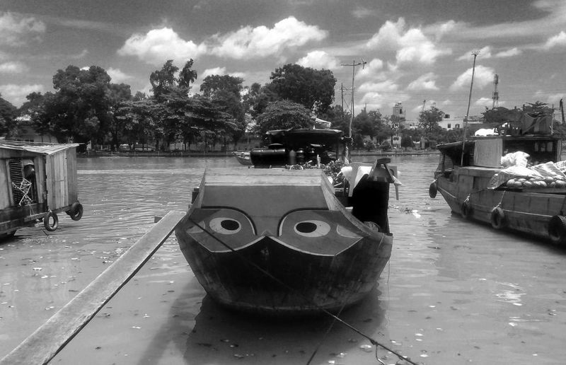 Boats moored on street in city against sky