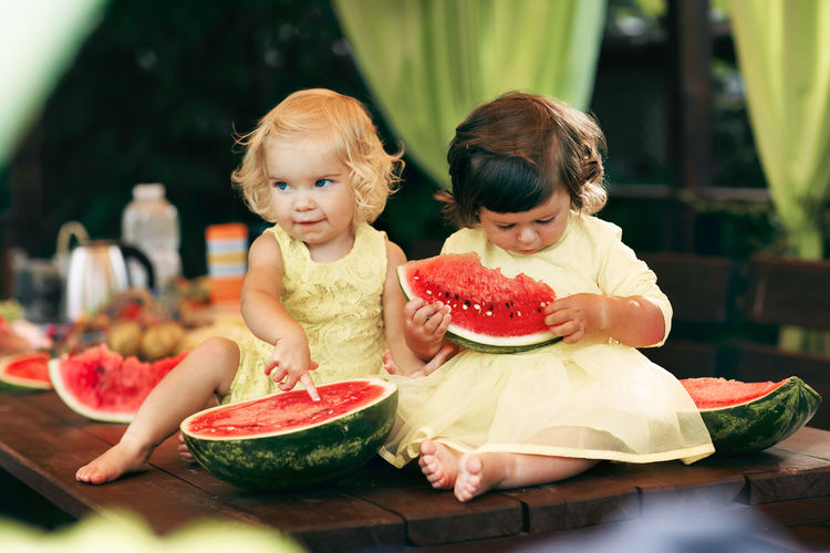 Girls eating watermelon on table
