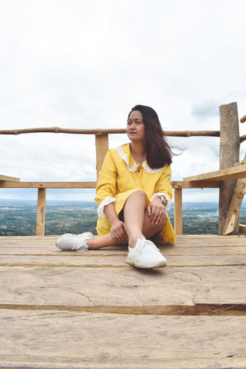 Young woman sitting on railing against sky