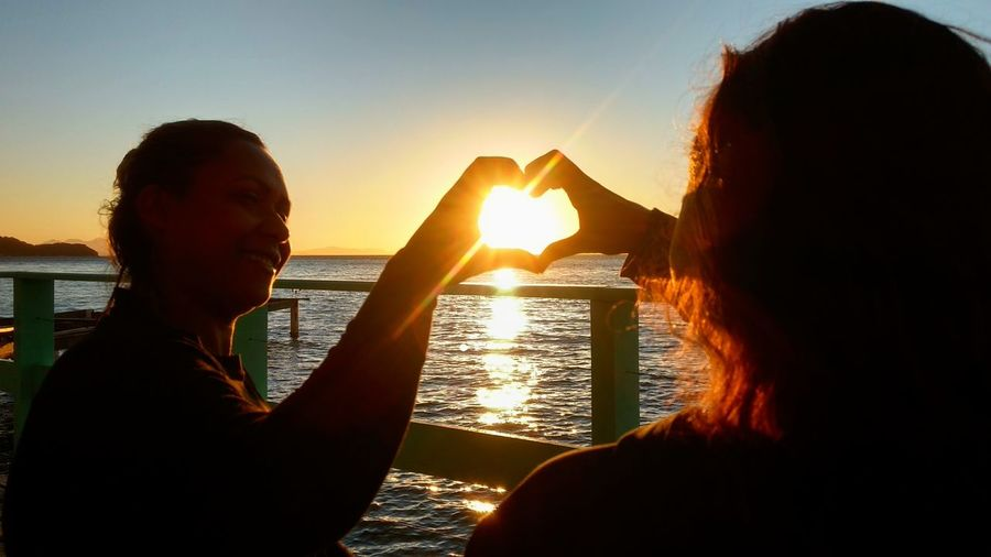 Hi heart hands Eyeem Market Portrait Photography Human Connection Young Women Water Friendship Sea Women Togetherness Sunset Happiness Bonding Smiling Silhouette Falling In Love Sunrise Horizon Over Water Romance Ocean Couple Coast Sun Shining
