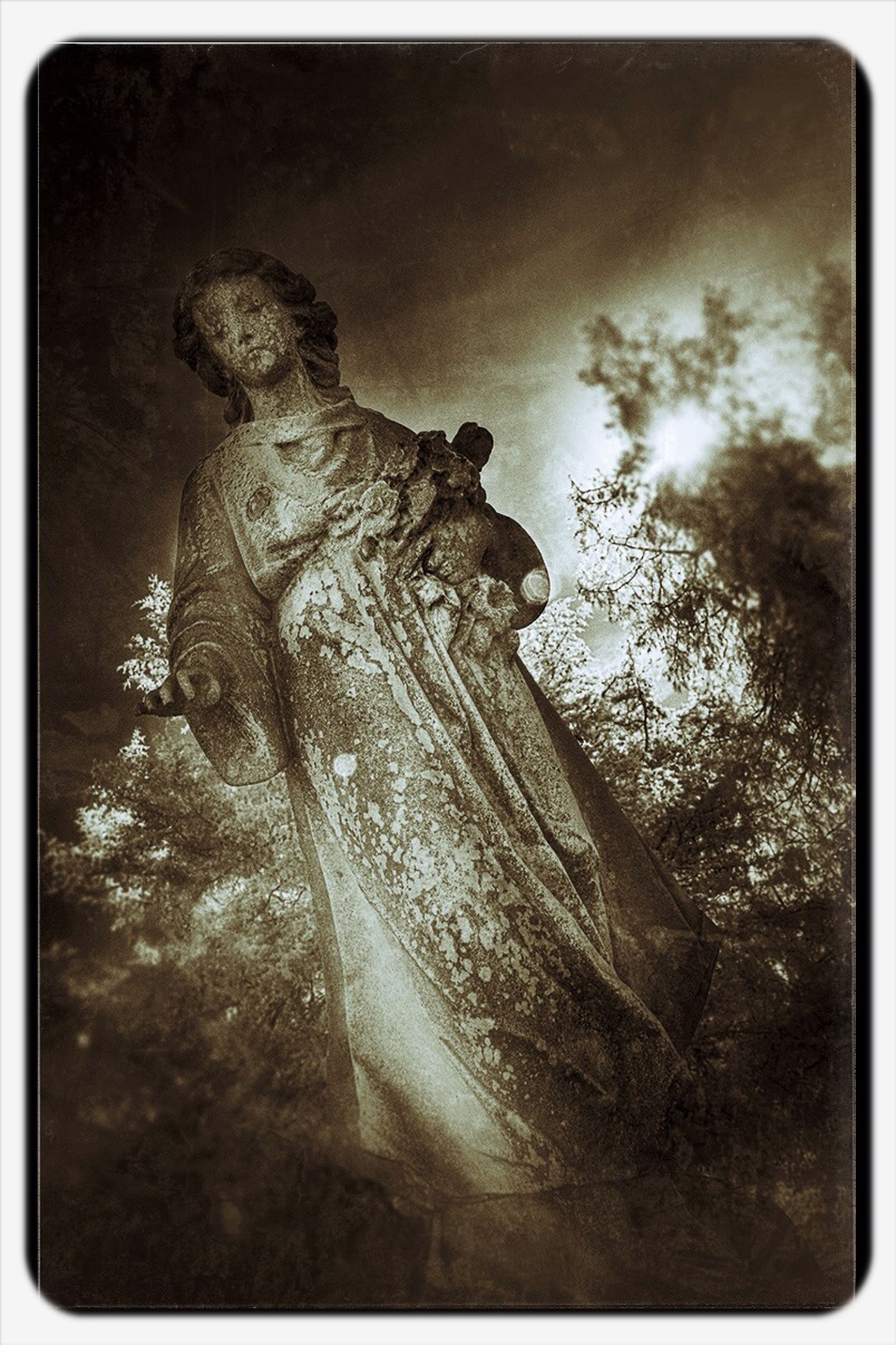 transfer print, auto post production filter, low angle view, sky, tranquility, statue, tree, nature, human representation, sculpture, tranquil scene, beauty in nature, weather, outdoors, day, no people, scenics, rock - object, mountain