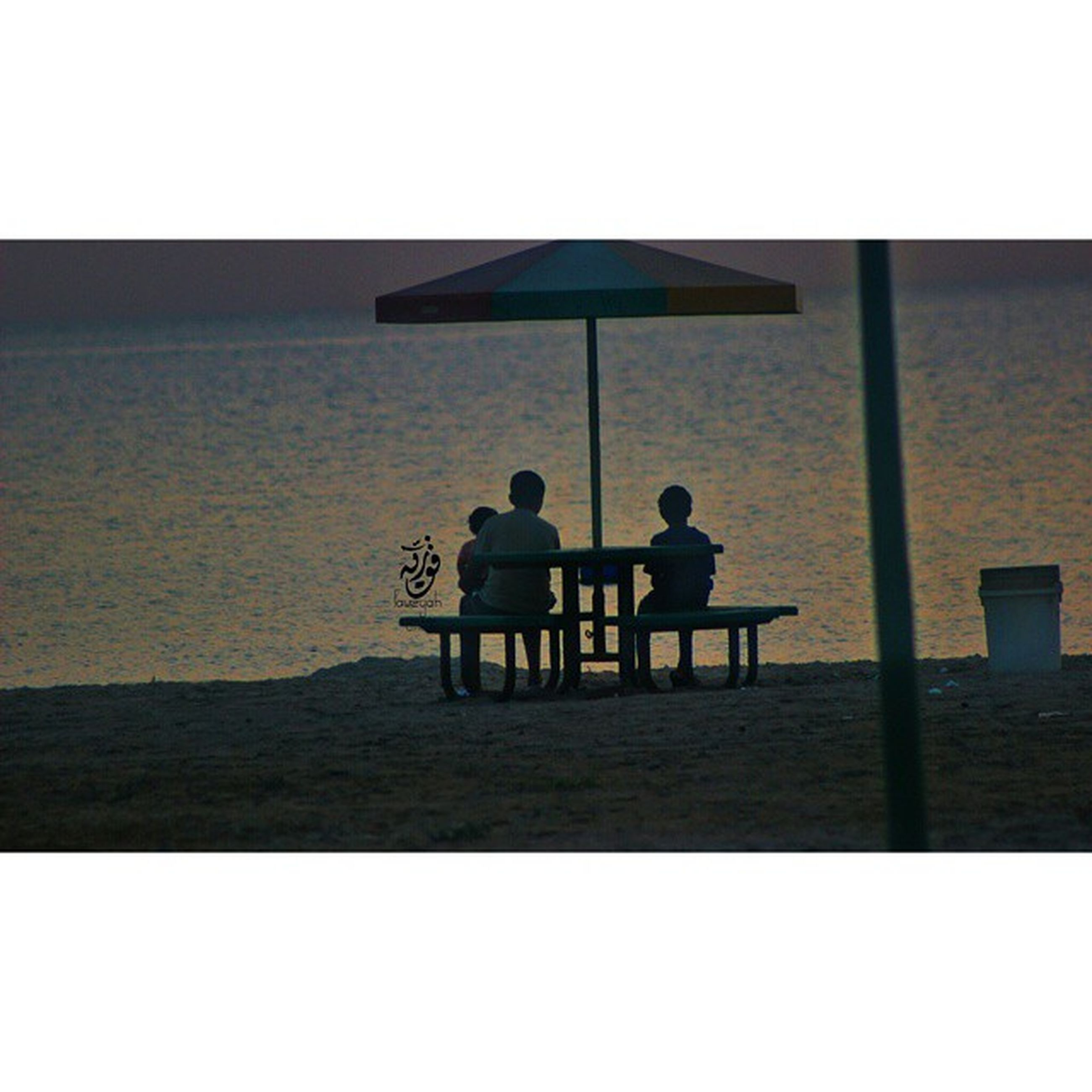 men, togetherness, lifestyles, leisure activity, bonding, sitting, rear view, transfer print, person, love, friendship, sea, water, silhouette, auto post production filter, built structure, full length