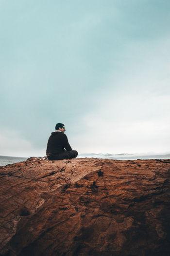 Rear view of man sitting on rock
