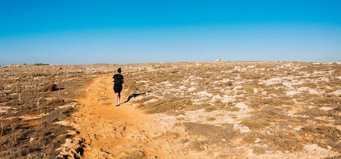 Rear view of woman walking on pathway against clear blue sky