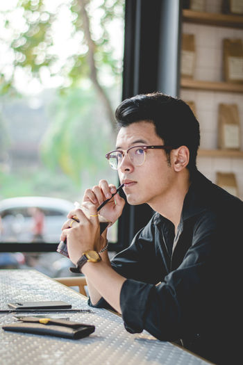 boy and coffee Adult Casual Clothing Contemplation Day Eyeglasses  Glasses Holding Males  Men One Person Outdoors Portrait Real People Side View Sitting Table Waist Up Window Young Adult Young Men