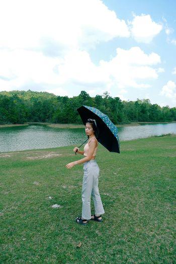 Full length of senior woman standing by lake against sky