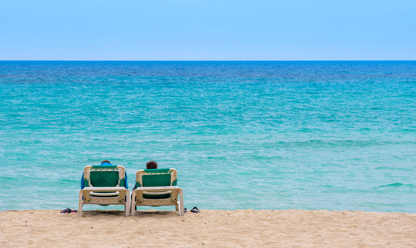 Lounge Chairs At Beach Against Clear Blue Sky