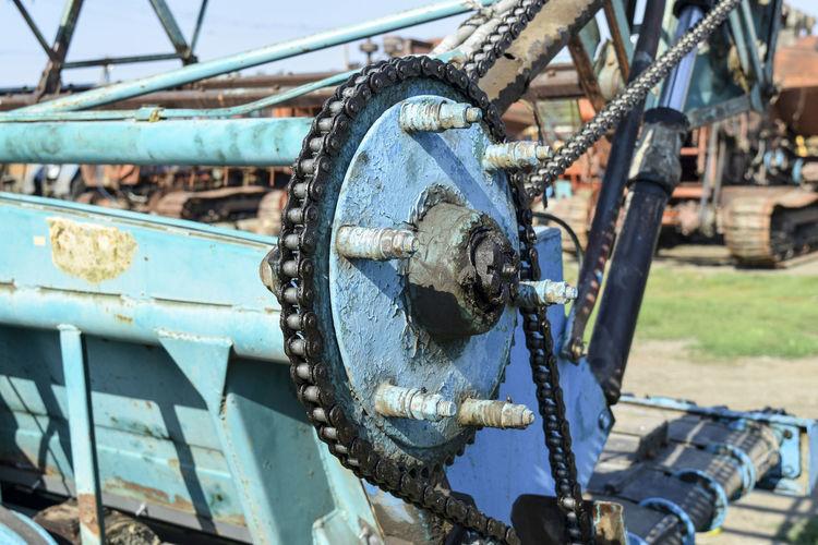 Close-up of rusty machinery on field