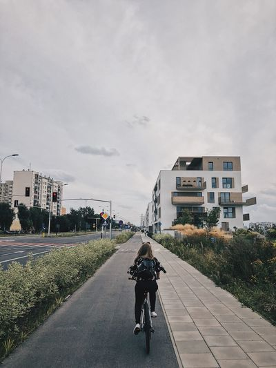 Rear view of people riding bicycle on road amidst buildings in city