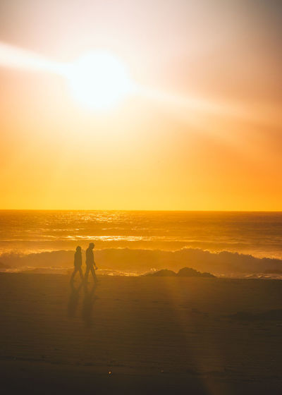 Silhouette couple walking at beach against orange sky