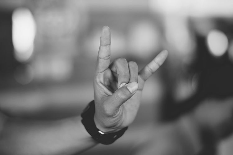 Cropped Hand Of Man Gesturing Horn Sign Outdoors