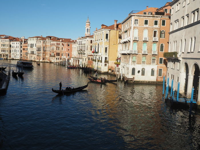 Architecture Building Exterior Built Structure Canal City Clear Sky Day Gondola Gondola - Traditional Boat Men Mode Of Transport Nautical Vessel Outdoors People Real People Residential Building Transportation Water Waterfront Wooden Post
