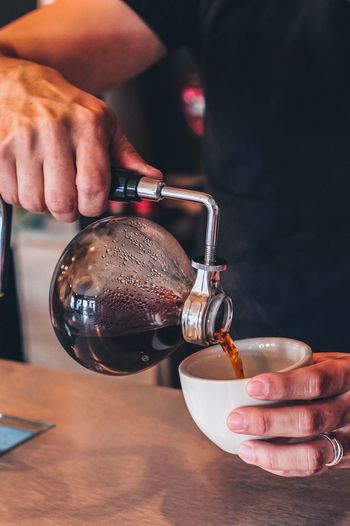 Cropped hands of man pouring coffee in cup at cafe