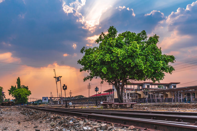 Railroad tracks amidst trees and buildings against sky during sunset