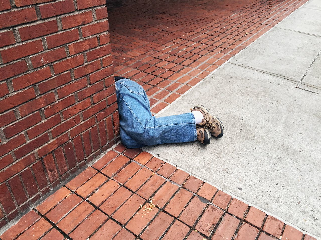Low section of person sleeping by brick wall