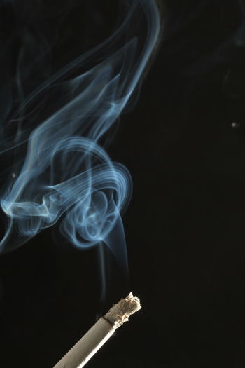 Close-up of cigarette against black background