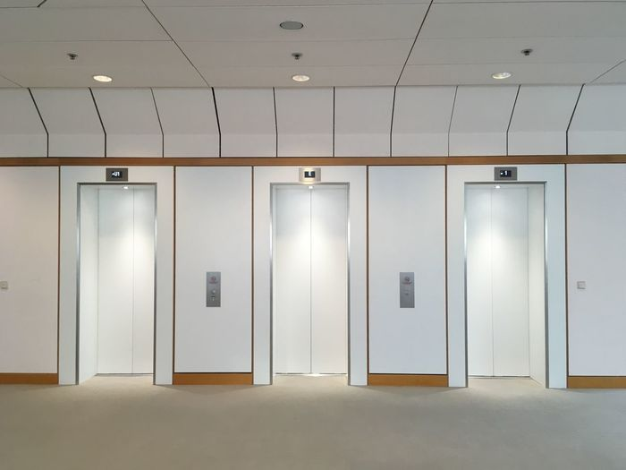 Elevator Indoors  Entrance Door Closed Architecture No People Communication Lighting Equipment Technology Built Structure White Color Illuminated Wall - Building Feature Locker Room Safety Hygiene Public Building Security Public Restroom Locker