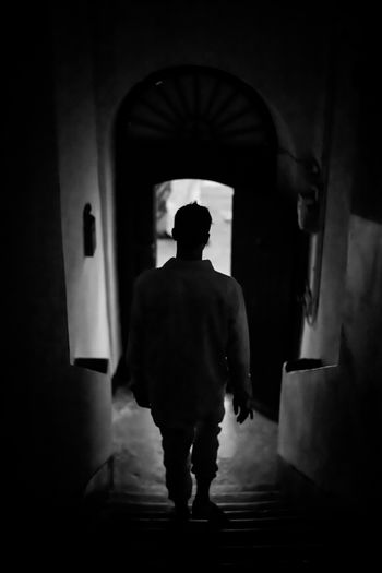 Rear view of man walking in building