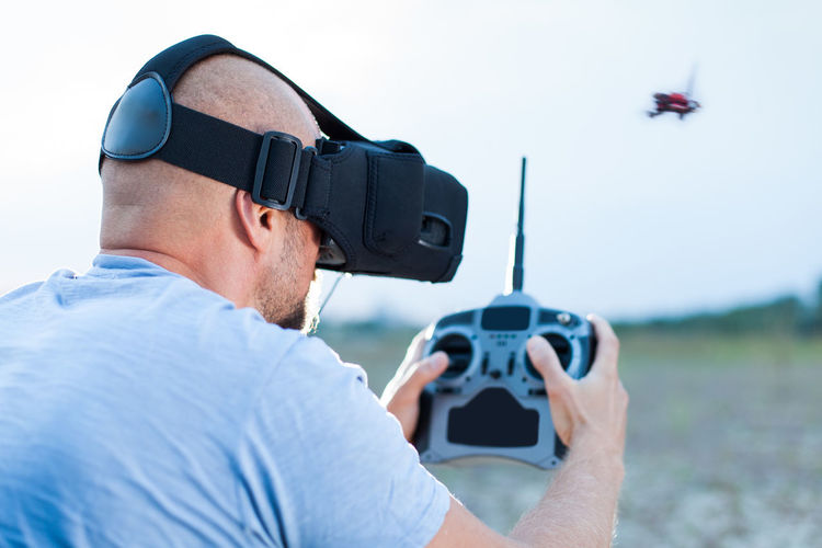 Man using virtual reality simulator while flying drone