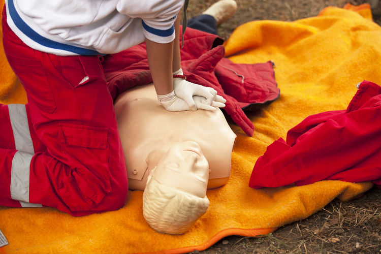 Paramedic practicing cpr on mannequin