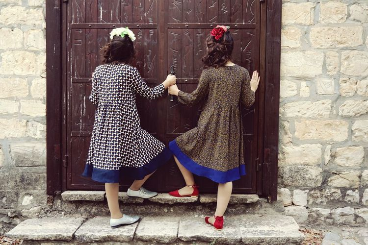 Rear View Of Two Girls Entering House