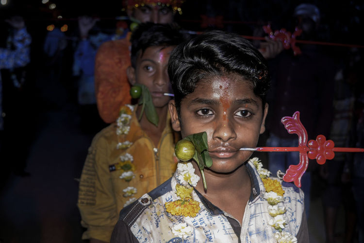 Close-up of boy with pierced metal through cheek during religious festival