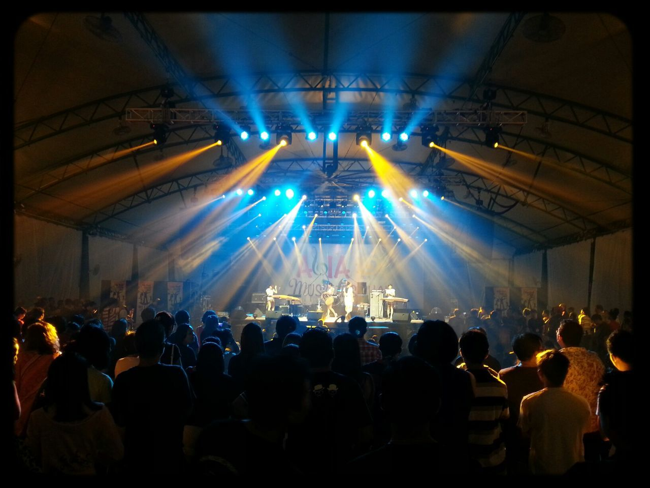 large group of people, crowd, illuminated, real people, indoors, arts culture and entertainment, men, music, women, stage - performance space, togetherness, audience, leisure activity, stage light, performance, youth culture, nightlife, night, popular music concert, musician, people
