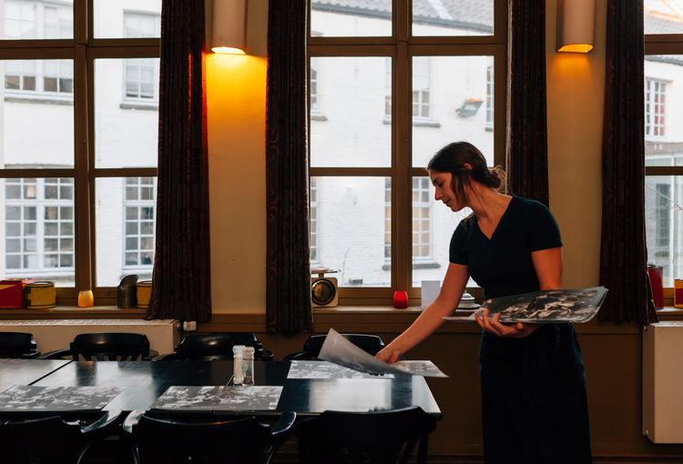 Waitress Setting Table At Restaurant