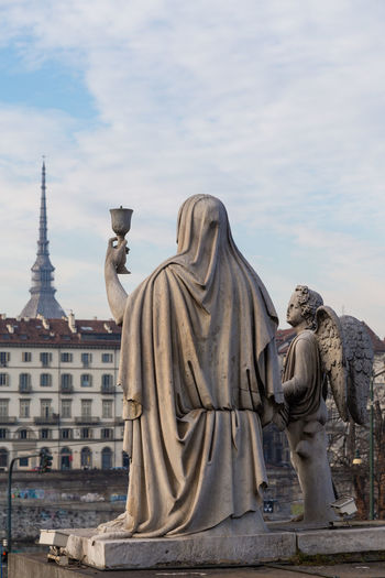 Statue in front of buildings at piazza vittorio veneto against sky