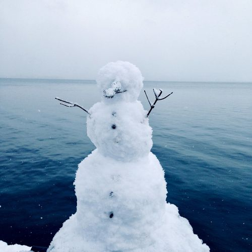 Frozen sea and snowman against sky during winter