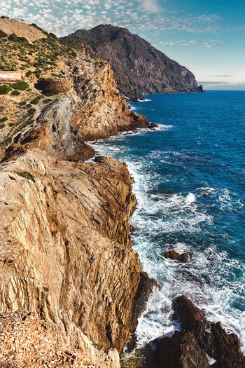 Scenic view of rocky coastline and sea against sky