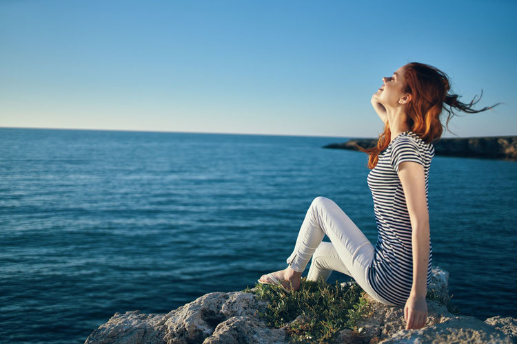 Woman sitting by sea against blue sky
