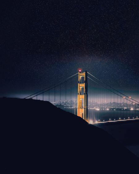 Golden gate bridge over bay against clear sky at night