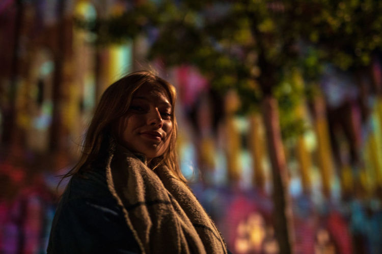 Portrait of smiling young woman standing outdoors at night