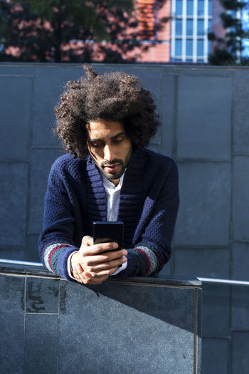 Young Man Using Phone While Standing In City