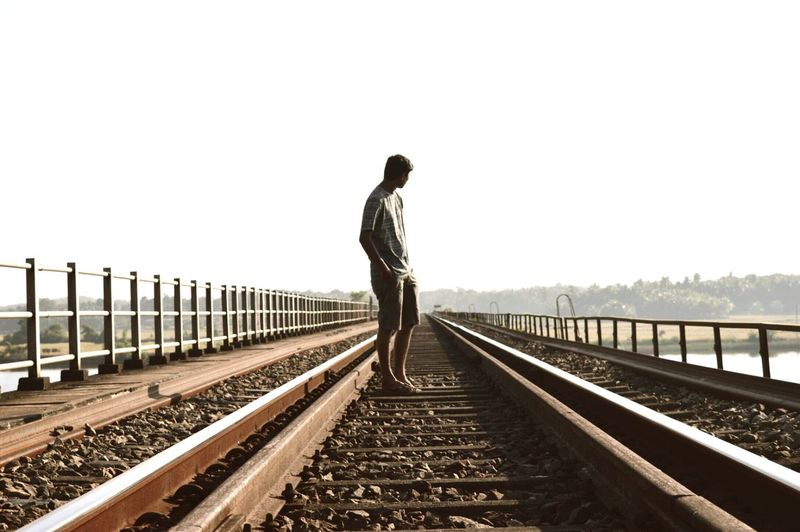 Side View Of Man Standing On Railroad Tracks Against Clear Sky