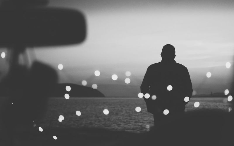Rear view of silhouette man in illuminated sea