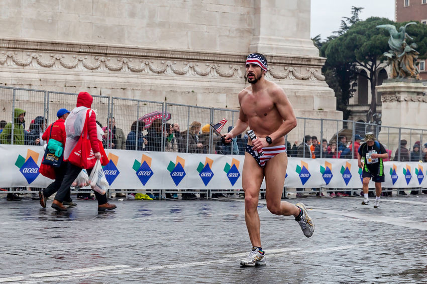 Rome, Italy - March 22, 2015: Rome Marathon 2015. A man in a bathing suit, competes with the colors of the American flag. Athlete Atletic Competition Day Daylight Fisico Italy Lifestyles Man Marathon Outdoors Rain Rome Runners Running Street Running Water