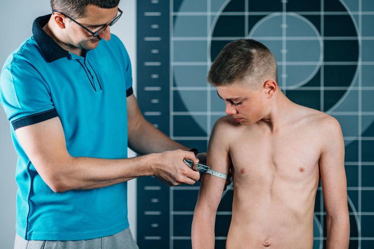 Man measuring shirtless male athlete bicep in health club