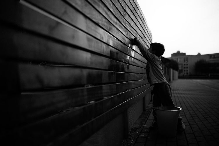 Boy cleaning wooden wall