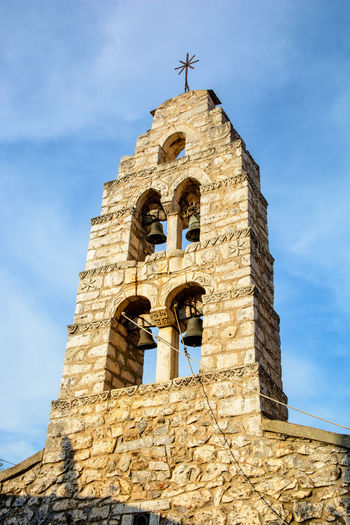 Low angle view of bell tower against sky